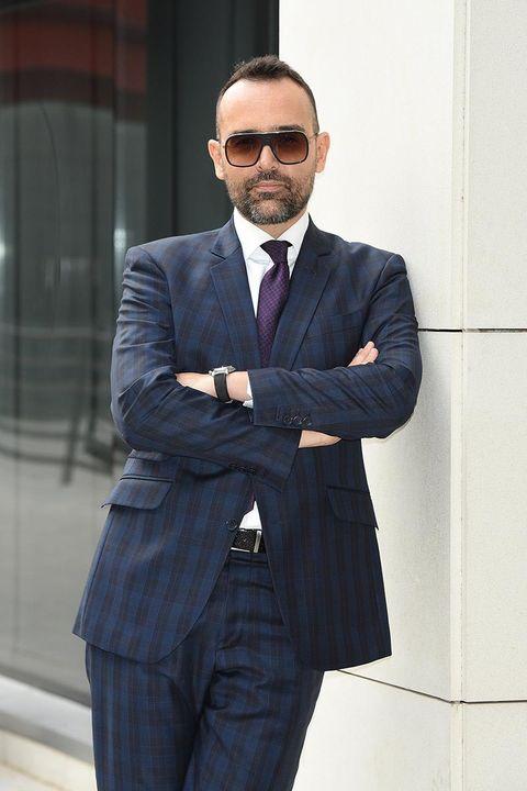 Suit, Formal wear, White-collar worker, Blazer, Tuxedo, Standing, Fashion, Businessperson, Outerwear, Tie,