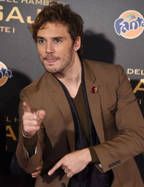 Arm, Finger, Hand, Collar, Wrist, Logo, Thumb, Dress shirt, Blazer, Facial hair,