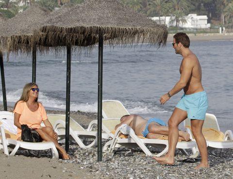 Leg, Fun, Thatching, Human body, Sitting, Leisure, Summer, Tourism, board short, People in nature,
