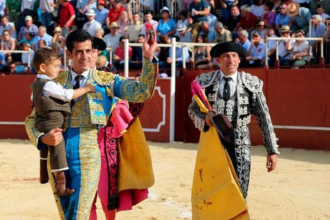 Matador, Hat, Bullring, Audience, Crowd, Tradition, Public event, Bullfighting, Sun hat, Costume,
