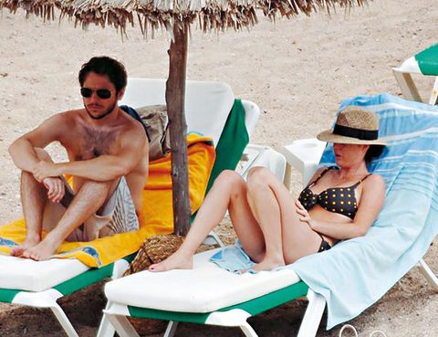 Eyewear, Leg, Sitting, Leisure, Summer, Hat, Comfort, Sun tanning, People in nature, Sunglasses,