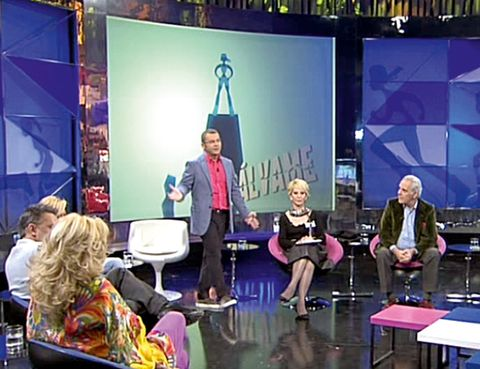 Furniture, Stage, Display device, Television program, Television presenter, Conversation, Television studio, Suit trousers, Media, Newscaster,