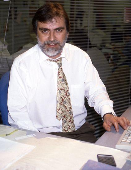 Dress shirt, Product, Collar, Facial hair, Shirt, Table, Moustache, Sitting, Beard, Tie,