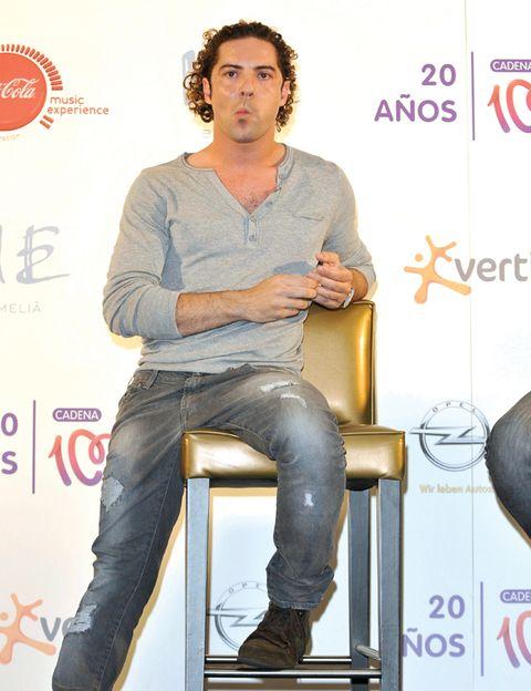 Leg, Denim, Jeans, Shoe, Sitting, Logo, Knee, Facial hair, Street fashion, Pocket,