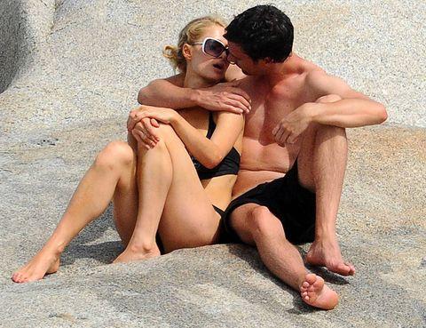 Eyewear, Vision care, Toe, Human leg, Sunglasses, Sitting, Barefoot, Summer, Sand, Slipper,
