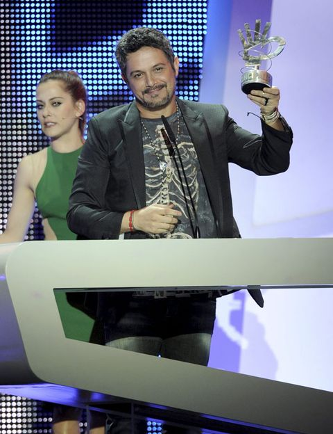 Trophy, Award, Award ceremony, Display device, Beard, Suit trousers,