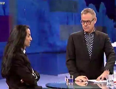 Arm, People, Formal wear, Coat, Television presenter, Interaction, Suit, Sitting, Blazer, Television program,
