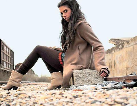 Shoe, Outerwear, Pebble, Sitting, Coat, Street fashion, Knee, Fashion, Beauty, Jacket,