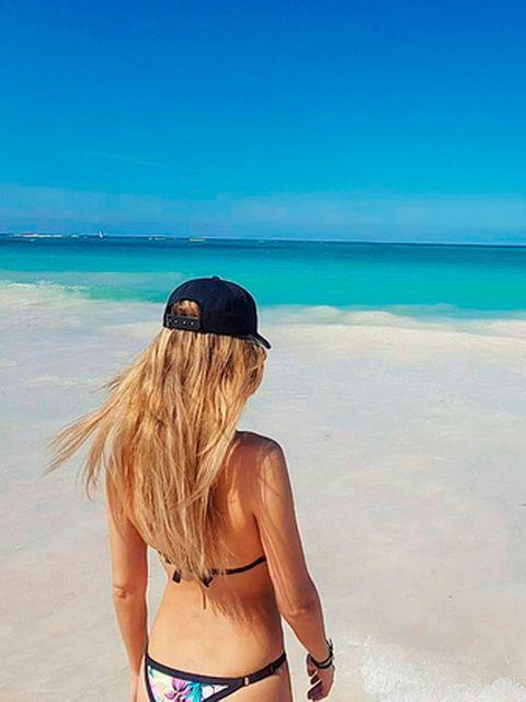 Blue, Hairstyle, Brassiere, Mammal, Summer, Swimsuit top, Aqua, Coastal and oceanic landforms, Beach, Back,