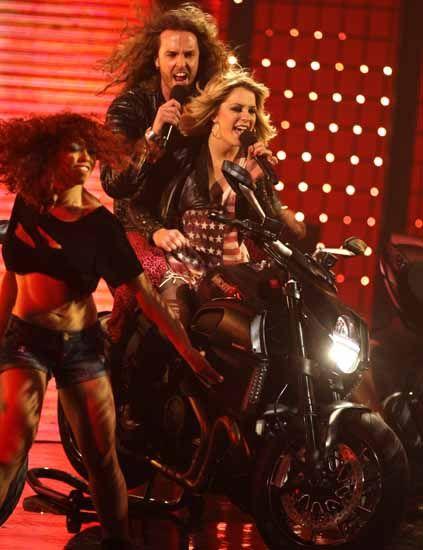 Motorcycle, Microphone, Fender, Motorcycle accessories, Boot, Long hair, Singing, Headlamp, Red hair, Singer,