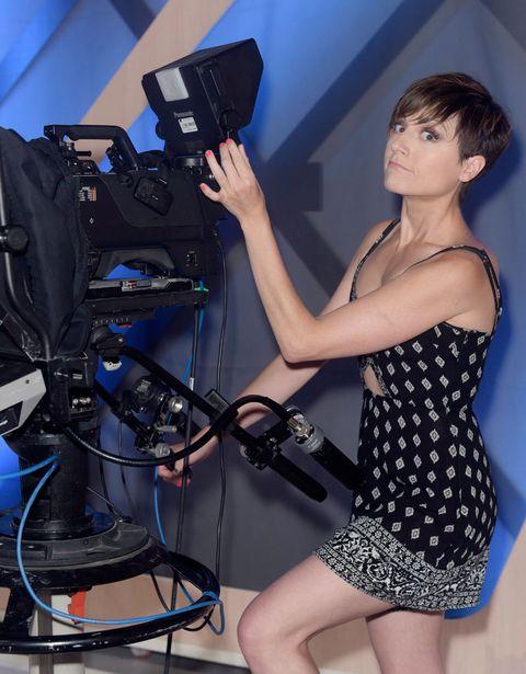 Dress, Standing, One-piece garment, Cameras & optics, Elbow, Filmmaking, Video camera, Cocktail dress, Day dress, Thigh,