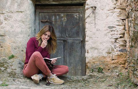 Wall, Sitting, Street fashion, Knee, Door, Long hair, Stone wall, Walking shoe, Outdoor shoe, Photo shoot,
