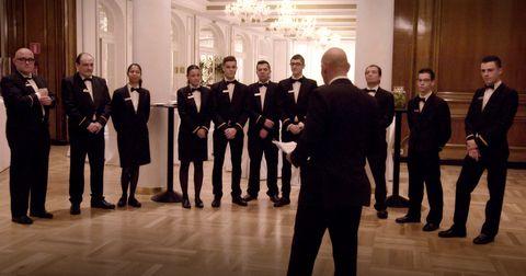 Footwear, Suit trousers, Social group, Suit, Formal wear, Team, Light fixture, Hall, White-collar worker, Tuxedo,