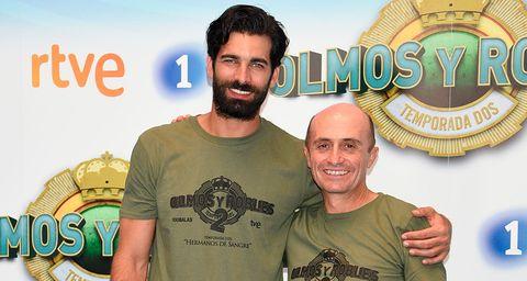 Mouth, Smile, Shirt, Facial hair, Facial expression, T-shirt, Logo, Beard, Tooth, Moustache,