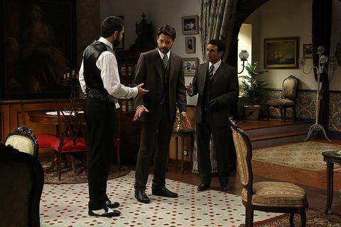 Suit trousers, Furniture, Coat, Suit, Formal wear, Blazer, Picture frame, Conversation, Drama, Living room,