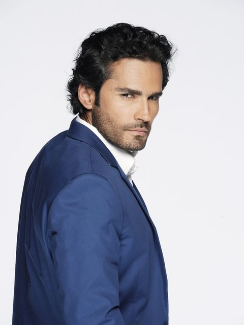 Clothing, Facial hair, Dress shirt, Hairstyle, Collar, Sleeve, Shoulder, Coat, Standing, Formal wear,