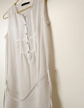 white sleeveless dress hanging on a hanger