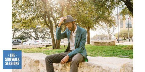 Hat, Coat, Trousers, Outerwear, Sitting, Blazer, Suit, Sun hat, Denim, Street fashion,