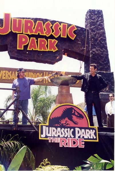 Steven Spielberg, who is reflecting the childlike wonder of his early work by dressing like a little boy, and Jeff Goldblum, who is wearing several layers of heavy black clothing to the opening of a water ride, light the eternal flame.