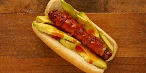 Is there any food avocado can't improve? Top this bacon wrapped dog with sliced avocado and hot sauce.