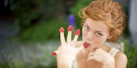 young woman eating raspberries