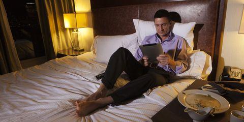 man reading tablet in hotel room