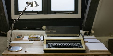 wooden desk with a typewriter and metal lamp