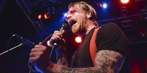 Eagles of Death Metal lead singer Jesse Hughes screams into a microphone on stage