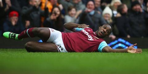 soccer player Michail Antonio lies on the ground of a soccer field