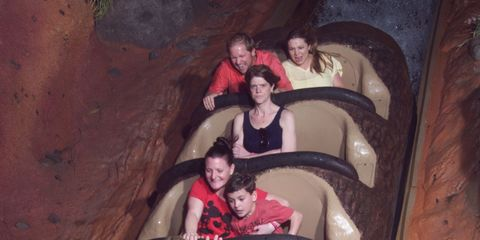 a woman riding Disney's Splash Mountain crosses her arms and stares menacingly at the camera while other riders are amused