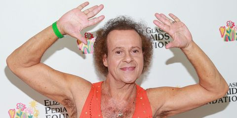 Richard Simmons raises his arms in the air