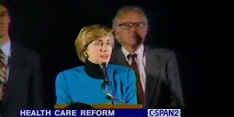 """still image of hillary clinton delivering a speech in 1993. bernie sanders stands behind her. a banner at the bottom of the image reads """"health care reform"""""""
