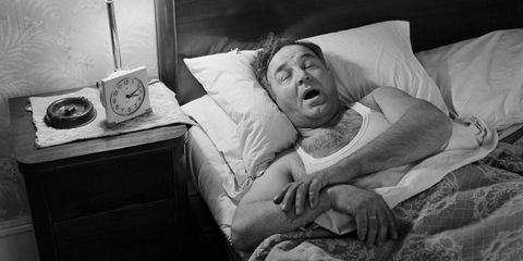 a man yawns in bed next to an alarm clock (black and white)