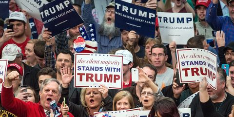 supporters cheer for Donald Trump holding signs