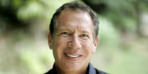 a headshot of Garry Shandling smiling against a green background