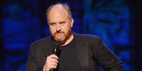 Louis C.K. holds a microphone and scowls