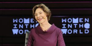 "Laura Bush smiles on stage in front of a sign that reads ""Women in the World"""