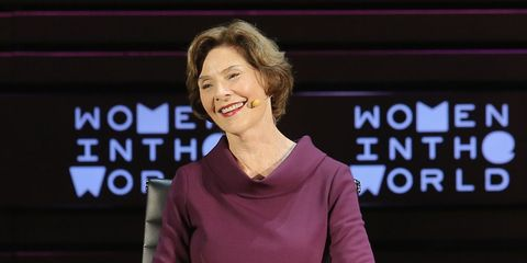 """Laura Bush smiles on stage in front of a sign that reads """"Women in the World"""""""