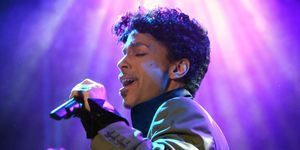 Prince holds a microphone and sings&#x3B; purple lights are in the background