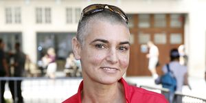 Sinead O'Connor in a red shirt smiles at the camera