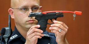 a police officer in court holds the gun that shot Trayvon Martin