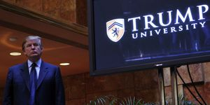 Donald Trump stands next to a television monitor with the Trump University logo