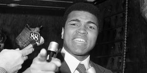 Muhammad Ali, speaking into microphones, points his finger at the camera