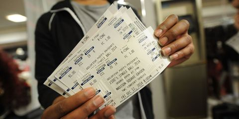 a man holds four concert tickets
