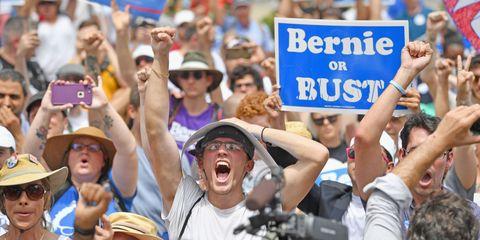 Nose, Hat, Crowd, Hand, Fashion accessory, Sun hat, Fan, Public event, Celebrating, Protest,