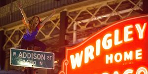 Chicago Cubs fan climbs street sign outside Wrigley Field
