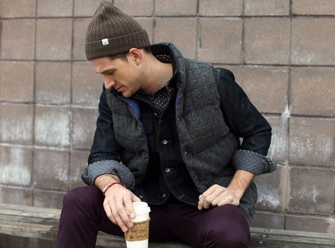 Cap, Human body, Sitting, Jacket, Hand, Outerwear, Coat, Street fashion, Knee, Brick,