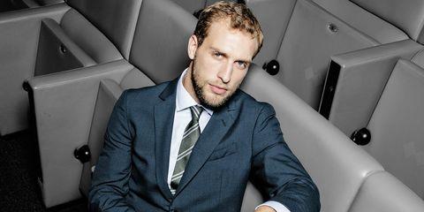 Dress shirt, Collar, Coat, Outerwear, Suit, Formal wear, Beard, Sitting, Blazer, Facial hair,