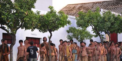 People, Human body, Standing, Community, Barechested, Temple, Muscle, Village, Tribe, Bermuda shorts,