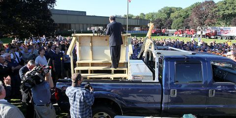 Pickup truck, Flag, Truck, Military person, Fender, Crowd, Uniform, Pole, Truck bed part, Marines,